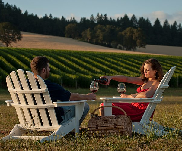 Man and Woman at Winery Sitting in Chairs Drinking Wine with a View