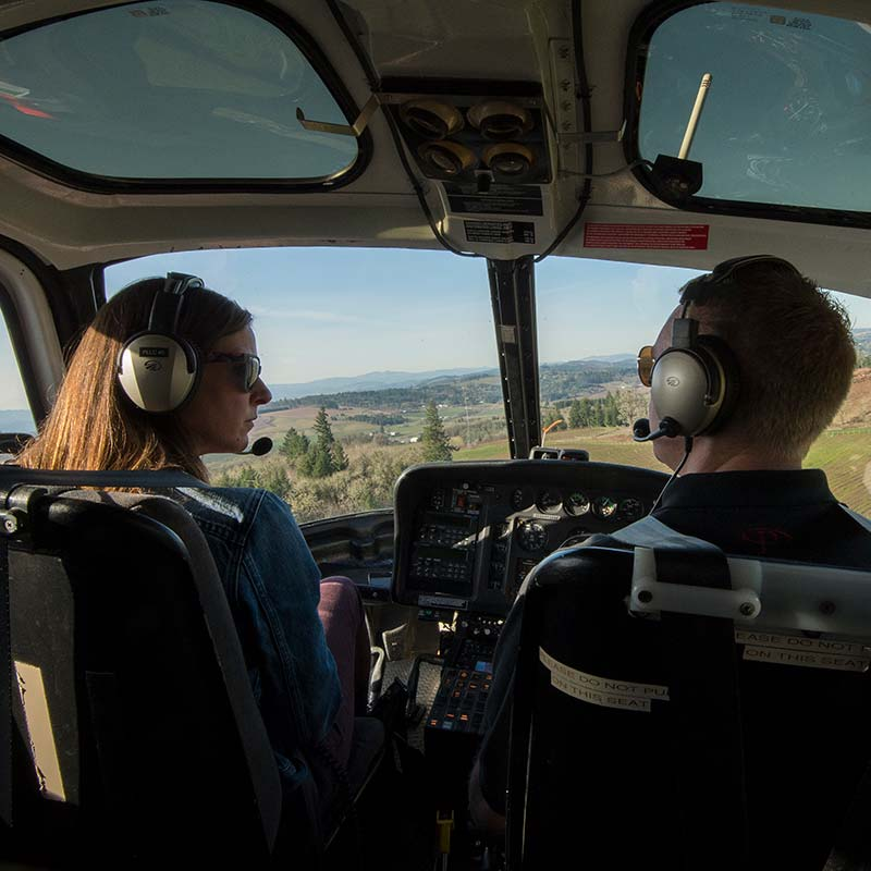 Woman and pilot talking in helicopter on a wine tour while flying over vineyard
