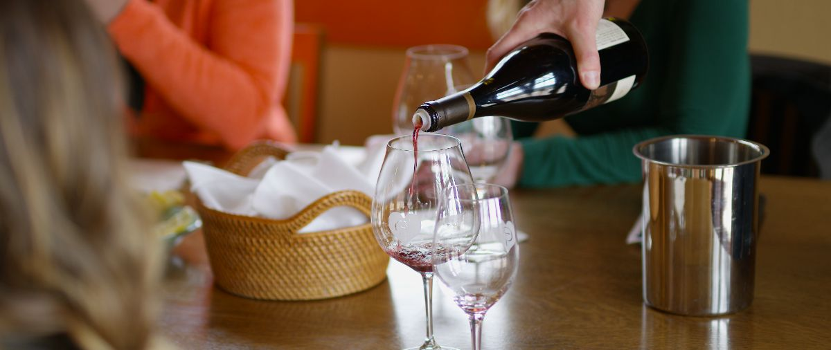 Pouring red wine at table during wine tasting tour