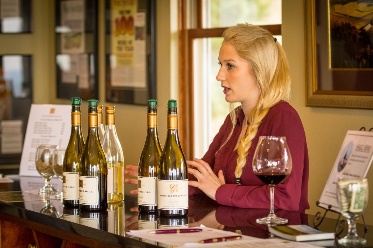 Winery staff woman explaining wine at wine tasting