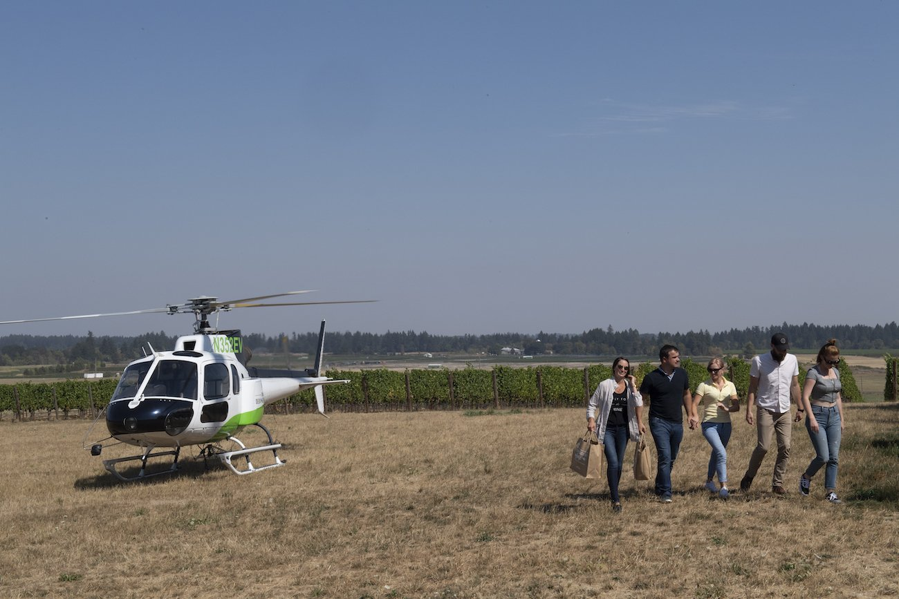 Group of wine tasters walking away from helicopter on Tour DeVine trip