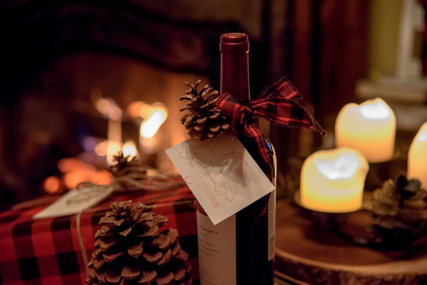 Wine gift wrapped for holidays near cozy fireplace