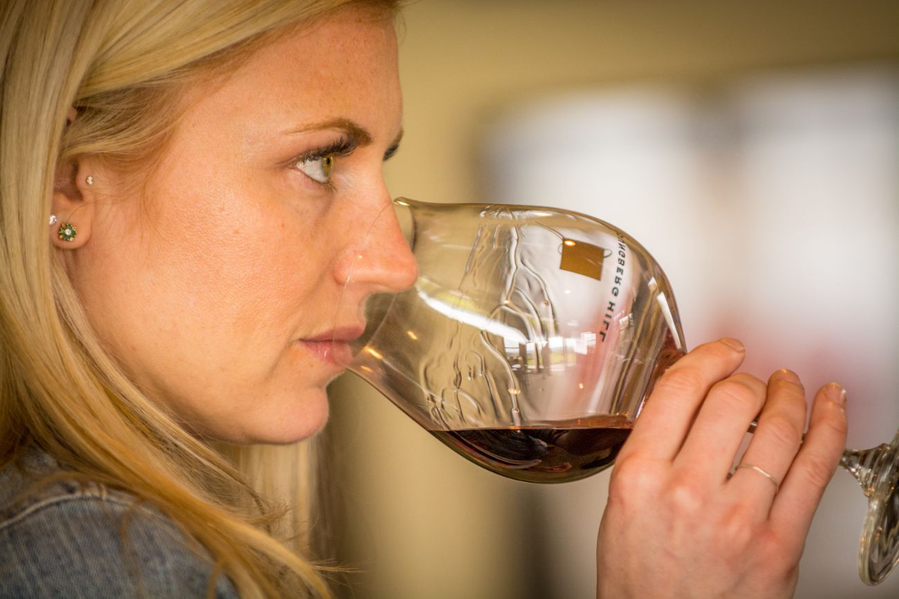 Woman smelling red wine at Youngberg Winery in Oregon