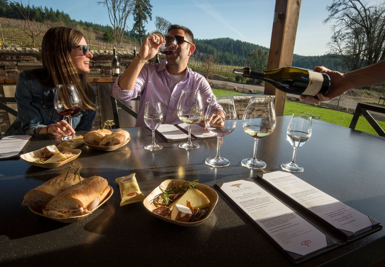 Couple tasting wine and eating lunch in Oregon