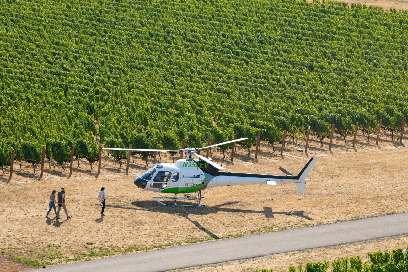 Tour DeVine guests walking towards helicopter in vineyard